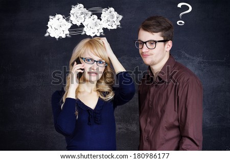 Portrait stressed couple going through hard times in relationship isolated grey background clouds above woman head question mark coming out of confused man. Upset girlfriend bringing bad news on phone - stock photo