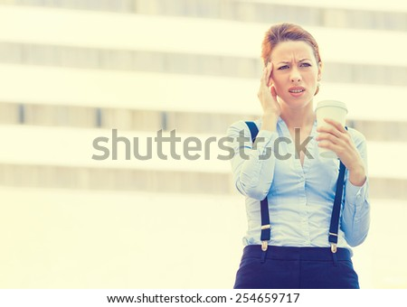 Portrait stressed worried young woman holding cup of coffee. Corporate employee having headache isolated outdoors corporate office window building background. Negative human emotions face expression   - stock photo