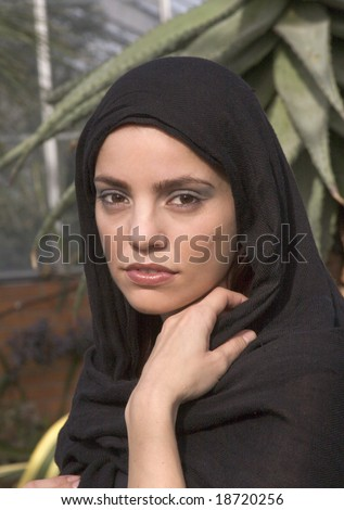 Portrait style shot of a beautiful woman wearing a headscarf or hijab - stock photo