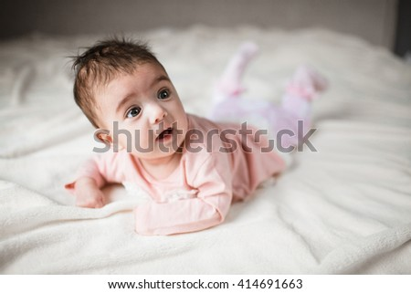 portrait surprised baby in bed - stock photo