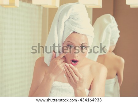 Portrait surprised middle aged woman looking in a mirror unhappy with wrinkles on her face. Skincare and aging concept. Human emotions face expression    - stock photo