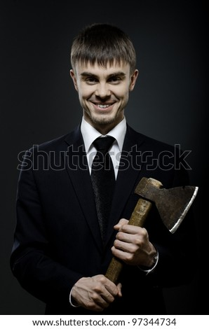 portrait  the  beautiful  businessman  in black costume and black necktie with axe, sinister look and smile - stock photo