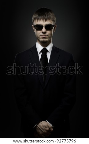portrait  the  beautiful  man in black costume,  special-service agent or  body guard - stock photo