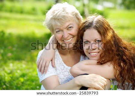 Portrait the daughter and elderly mother in park - stock photo