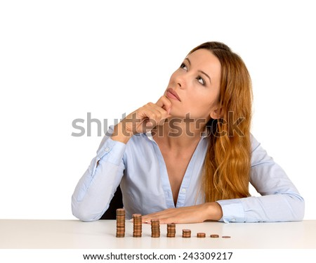 Portrait thoughtful young business woman corporate executive sitting at table with growing stack of coins isolated on white background. Face expression. Financial economy banking savings concept - stock photo