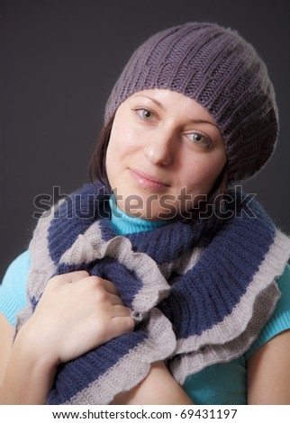 Portrait to the young woman in a cap with a scarf on a black background - stock photo