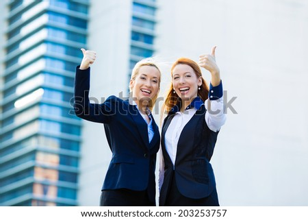 Portrait two attractive, beautiful smiling business women standing, isolated on corporate office building background giving thumbs up. Positive human emotions, face expressions, signs, symbol attitude - stock photo