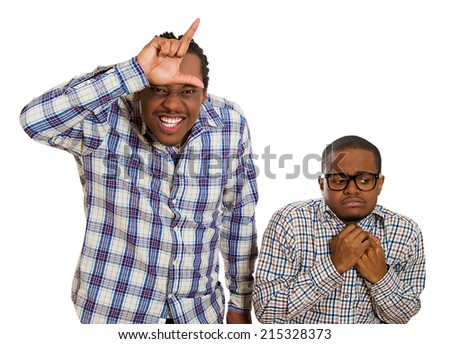 Portrait two young men, rude bully standing upfront showing looser sign, shy little nerd guy wearing glasses standing anxiously isolated white background. Human emotions, attitude, life perception - stock photo
