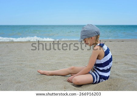 Portrait very serious cute little girl in striped dress sitting on the beach - stock photo