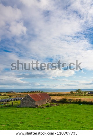 Portrait view of a barn in a green field and the atlantic ocean backdrop in picturesque Northern Ireland - stock photo