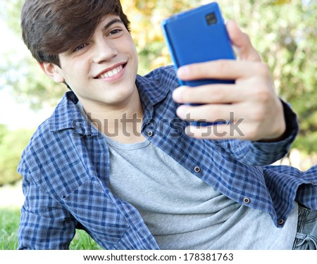 Portrait view of a teenager student boy laying down in a park with his college books, using a smartphone to take a selfie photo of himself for networking, posing and smiling. Technology lifestyle. - stock photo