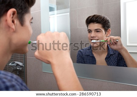 Portrait view of a young man brushing his teeth in a home bathroom, looking at his own reflection getting ready for college, home interior. Health and well being teeth care and grooming, indoors. - stock photo