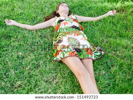 Portrait view of a young woman laying down on green grass with her arms outstretched, relaxing while feeling nature during a sunny summer day, outdoors. - stock photo