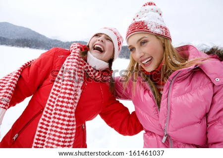 Portrait view of two joyful young women friends having fun and laughing while on a skiing holiday in a white snow  landscape scenery in the mountains, laughing with big expressions, outdoors. - stock photo