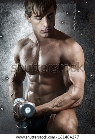 Portrait with naked athletic torso of young beautiful man with dumbbells  - stock photo