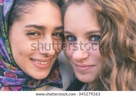 Portrait with two girls from different ethnicity. Muslims and christians people perfectly integrated - stock photo