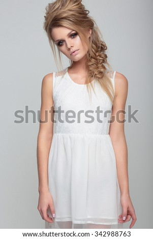 Portrait woman with creative hairstyle and in a white dress. - stock photo