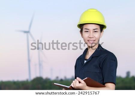 portrait women asia engineer working and holding blueprints at wind turbine farm Power Generator Station - stock photo