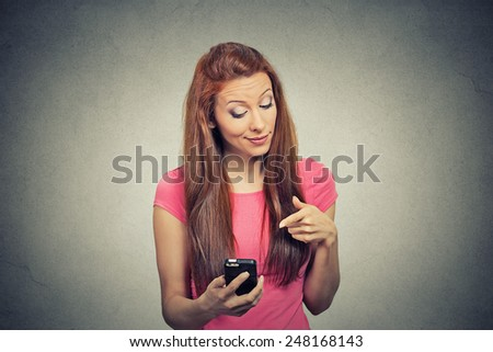 Portrait young angry woman unhappy, annoyed by something, someone on her cell phone while texting, receiving bad sms text message isolated grey wall background. Human face expression emotion reaction - stock photo