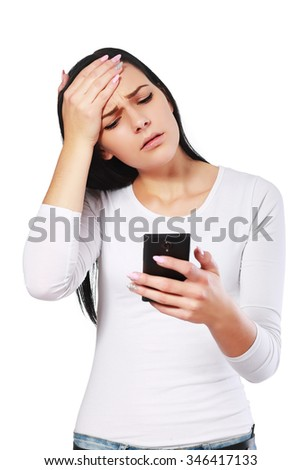 Portrait young angry woman unhappy, annoyed by something, someone on her cell phone while texting, receiving bad sms text message isolated whitel background. Human face expression emotion reaction - stock photo