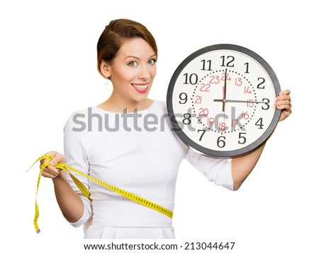 Portrait young attractive, happy, fit woman in white dress, holding clock, measuring her waist with tape, isolated white background. Weight loss program results with time. Positive face expression - stock photo
