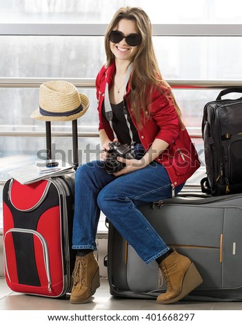 portrait young attractive woman in a red jacket and sunglasses sitting on suitcases in the terminal or train station. The girl met on a trip. She looks into the camera and smiling. - stock photo