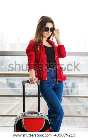 portrait young attractive woman in red standing in the terminal with the glasses with a suitcase. The girl met on a trip. - stock photo
