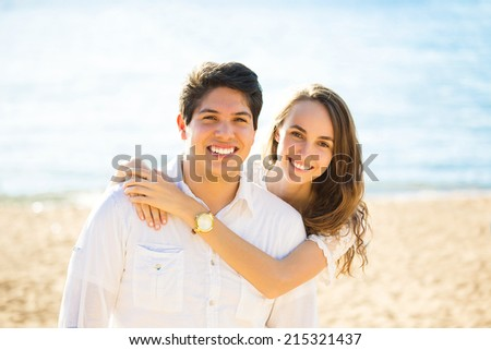 Portrait young beautiful smiling couple by the sea on a sunny summer, autumn day.  Positive human emotions, facial expressions, feelings, life perception. Happy lifestyle, romantic getaway - stock photo