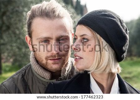 Portrait. Young blond man in a park and a girl with blond hair  - stock photo