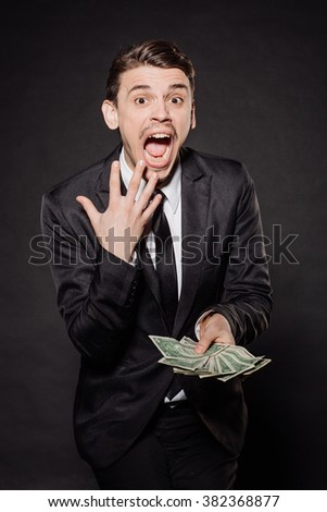 portrait young businessman in black suit holding group of dollar bills. emotions, facial expressions, feelings, body language, signs. image on a black studio background. - stock photo