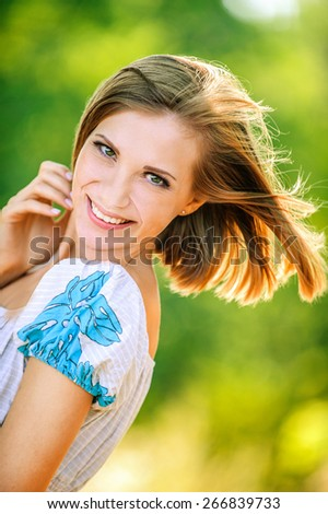 portrait young cheerful woman shorthair peeps background summer green park - stock photo