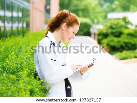 Portrait, young confident female doctor, healthcare professional reading patient chart isolated background outside hospital, green trees. Patient visit health care. Positive facial expression attitude - stock photo