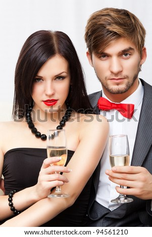 Portrait young couple with glass of champagne, wear evening dress red lips and suit with red bow, glamour vogue style, sensual looking at camera, sitting indoors - stock photo