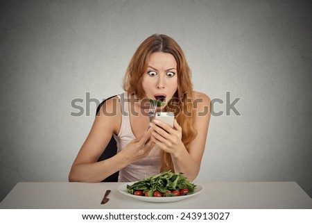 portrait young girl eating green salad looking at phone seeing bad breaking news or photos shocked confused face expression isolated on grey wall background  - stock photo