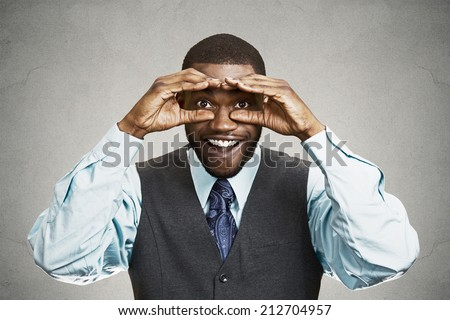 Portrait young handsome man, looking curious, surprised, shocked through fingers like binoculars searching something, future direction isolated grey background. Positive face expression emotion  - stock photo