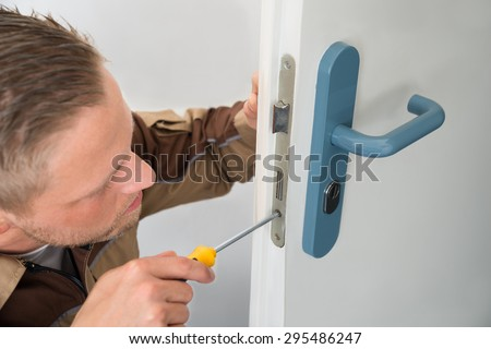 Portrait Young Male Carpenter Repairing Door Lock - stock photo