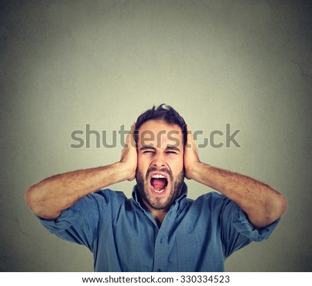 Portrait young man screaming mouth open, holding head with hands, wearing casual blue shirt, isolated on gray wall background. Human face expression emotion - stock photo