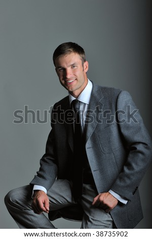 portrait young serious businessman, looks in chamber, on gray background - stock photo