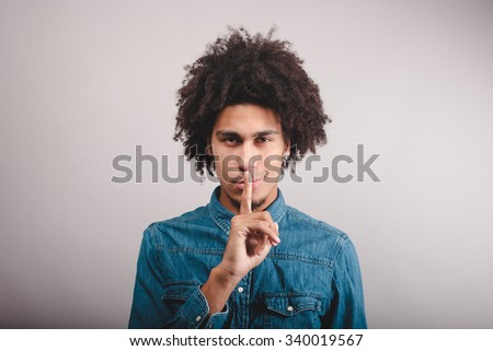 portrait young serious man placing finger on lips saying, shhh, be quiet - stock photo