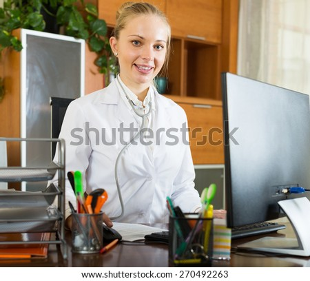 Portrait young smiling of female doctor in clinic office - stock photo