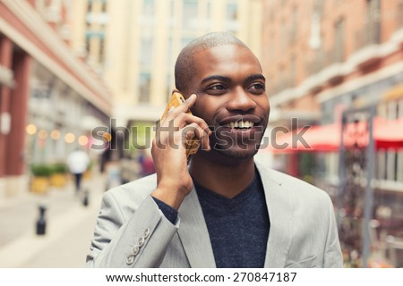 Portrait young urban professional smiling man using smart phone - stock photo