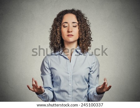 Portrait young woman meditating isolated on grey office wall background. human face expression emotion signs symbols  - stock photo