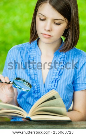 Portrait young woman short hair close-up reading book magnifier at summer green park - stock photo