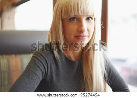 Portrait young woman sitting in cafe - stock photo