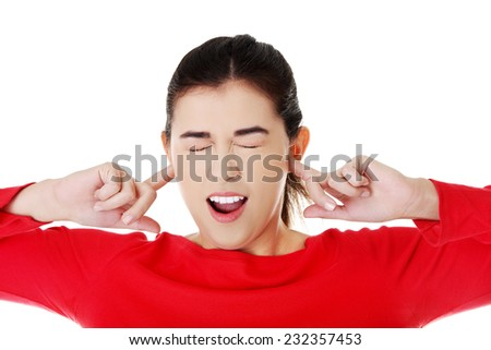 Portrait young woman with fingers in ears. - stock photo