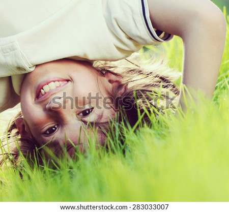 Portraits of happy kids playing upside down outdoors in summer park walking on hands - stock photo