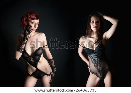 Portraits of two beautiful women in erotic lingerie, photo in front of black studio background - stock photo
