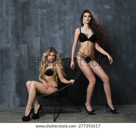 Portraits of two beautiful women in erotic lingerie, photo in front of blue studio background - stock photo