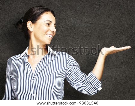 portrat of a middle aged woman holding gesture against a grunge background - stock photo