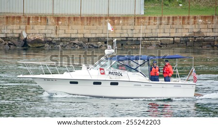 Portsmouth, NH, USA - August 2, 2014: A US Coast Guard patrol boat heads up the Piscataway River near the Portsmouth Naval Shipyard on this summer afternoon. - stock photo